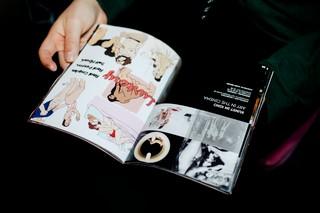 Frau blättert durch Broschüre mit Comics beim Sex