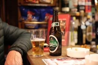en ølflaske og et glas i baren på et værtshus.
