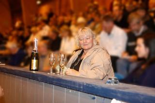 Britta Nielsen sidder ved en bardisk med en flaske champagne og to glas.