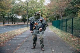 Der Autor steht in seinem Tarn-Anzug auf dem Bürgersteig.