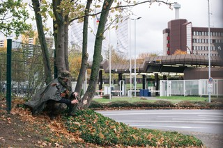 Der Autor kauert an einem Hügel und beobachtet den Eingang zum Bundesamt für Verfassungsschutz