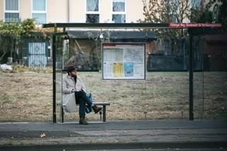 Der Autor sitzt in neuer Tarnung an einer Bushaltestelle
