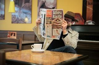 Der Autor sitzt im Kaffee und liest eine Zeitung – doch die Zeitung hat ein Loch!