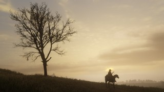 A barren tree juts from a hillside at the left of the frame, silhouetted against a sky turning tan and gold with the sunset, while further down the slope sits a solitary horseman.
