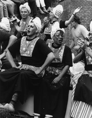 1541667781065-Groep-homomannen-en-twee-vrouwen-verkleed-meisjes-in-Nederlandse-klederdracht-op-klompen-tijdens-de-Gay-Pride-1996-canal-parade-in-Amsterdam-Gon-Buurman