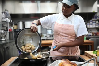 Ashley Eddie adding potatoes to skillet
