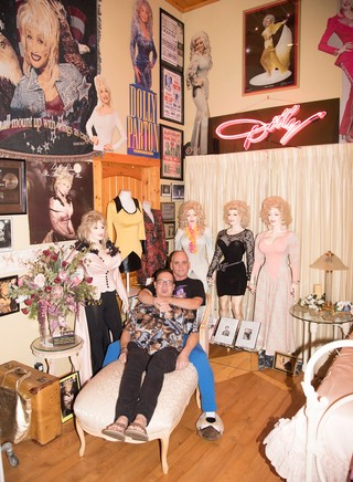 Patric and Harrell sit in front of a section of their Dolly Parton collection, featuring mannequins in Dolly outfits, and framed photos of the singer.
