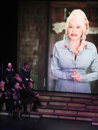 Relatives of Dolly Parton performing onstage alongside a projection of Dolly