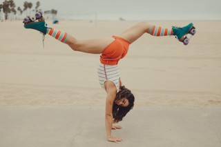 Michelle doing a split-leg handstand