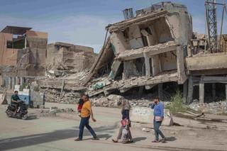 Fußgänger laufen an Gebäuden in Mossul vorbei, die während des Kampfes gegen den IS zerstört wurden