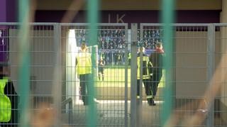 Sicherheitskräfte und Ordner hinter einem der Durchgänge im Fußballstadion