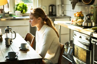 Julie sidder ved spisebordet i køkkenet og drikker kaffe