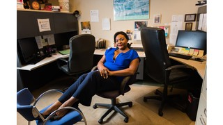 A black women in a blue shirt and black pants reclining in an office chair