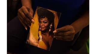 Hands holding film portrait of black woman in dress and earrings.