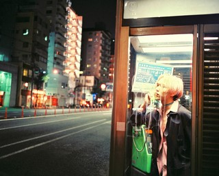 James J. Robinson photographs a man in a phone booth