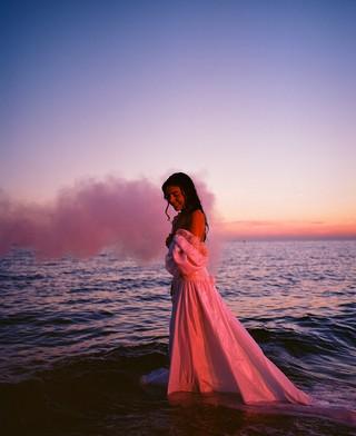 James J. Robinson photographs woman in a dress on the beach