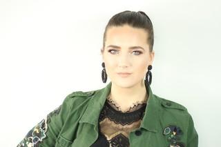 Vrouw kijkt in camera groene jas aan