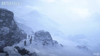 A squad of soldiers walk up a snowy mountain pass in a blizzard.