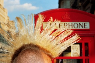 Martin Parr photographs a mohawk in front of a red telephone box