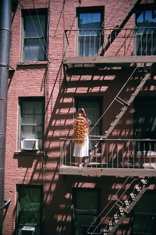 a model stands on a FIRE ESCAPE photographed by sabrina santiago