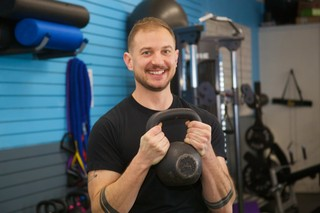 a man lifting a kettlebell