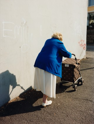 maxwell tomlinson photographs an old woman walking down the street