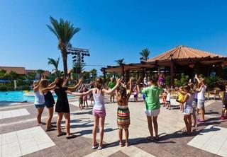 Kinder stehen am Pool in einem Kreis und halten die Hände in die Höhe