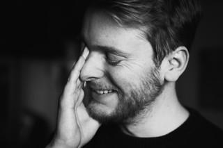 Mads Holm smiler med lukkede øjne og rører sig selv i ansigtet