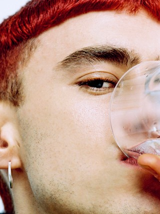 olly alexander drinking a glass of water