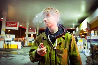 En ung mand på en tankstation. Han har lyst hår, er iført armygrøn jakke og ryger en cigaret