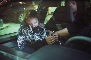 En pige sidder i en bil og griner med sin telefon i hånden