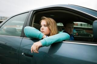 en ung pige kigger ud af vinduet fra passagersædet i en sort bil