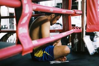 Trainer Chai zit in de ring op zijn telefoon, wachtend op de volgende privéles.