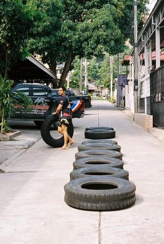 De autobanden worden klaargelegd voor de groepsles. Een minuut of tien springen op autobanden hoort bij de warming-up.