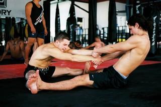 Wedstrijdvechters Marvin en Nicholas rekken elkaars benen op tijdens een vroege ochtendtraining.