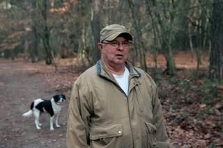 Ein Mann und ein Hund stehen auf einem Waldweg in Müggelheim