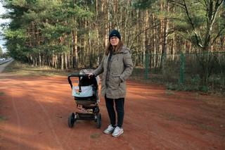 Eine junge Frau mit einem Kinderwagen steht auf einem Weg vor den Kiefern von Müggelheim