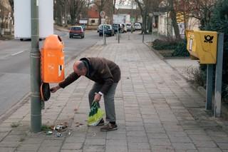 Ein alter Mann begutachtet einen kaputten Straßenmülleimer in Müggelheim
