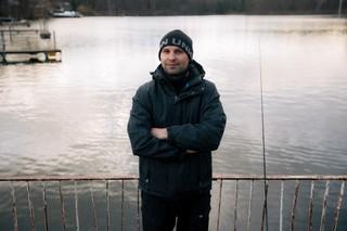 Ein Angler lehnt an ein Geländer am See in Müggelheim