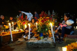 A family sits around their relatives gravestones late into the night