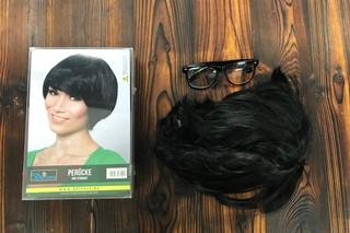 Ein Wes-Anderson-mäßiges Bild von einer Perücke und einer Brille