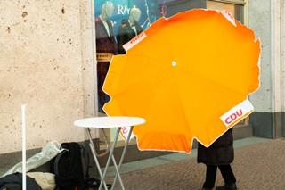 Jemand hantiert mit einem CDU-Sonnenschirm auf dem Alexanderplatz