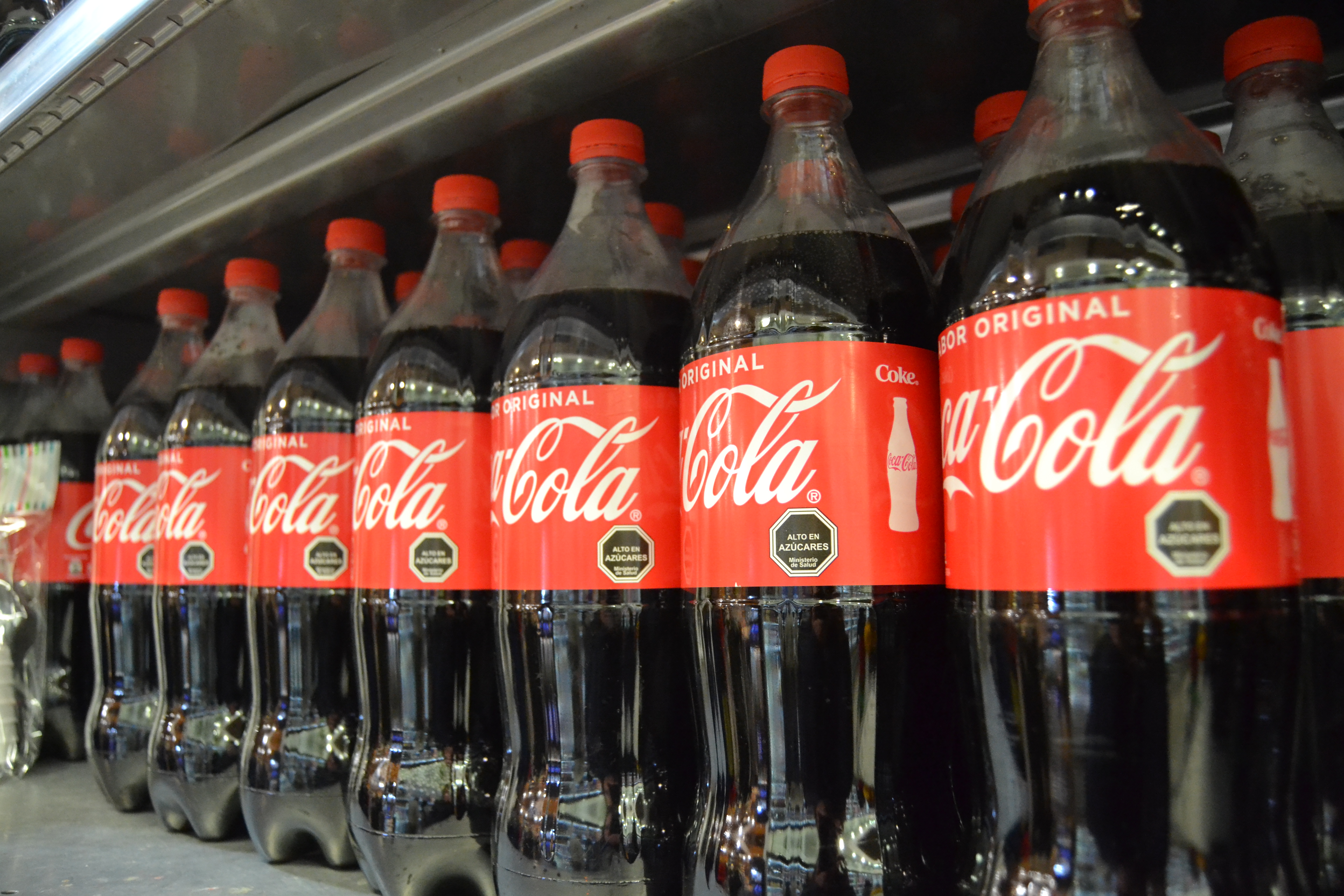 Coca Cola bottles with black labels indicating high sugar content.