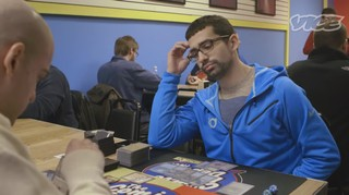A still frame from a Vice documentary depicting a man in a blue hoodie staring contemplatively at a table covered in Magic cards.