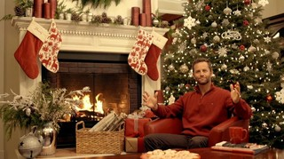 Kirk Cameron sitting in front of a Christmas tree