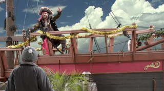 A man dressed as a pirate, standing on a pirate ship.