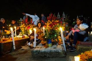 Eine Familie sitzt am geschmückten Grab ihrer Verwandten
