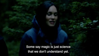 Megan Fox walking through a forest. A subtitle says