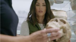 Megan Fox examining a skull