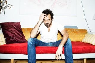 Hassan Preisler sidder i sin sofa og ser vred ud